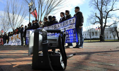 Pro-democracy protesters opposed to the Chinese government use a bullhorn as they stand on the sidewalk outside the White House in Washington