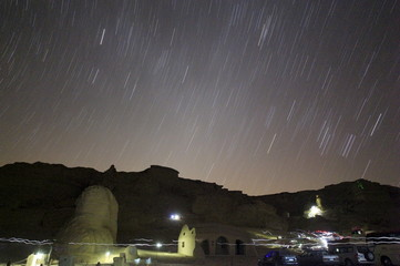 A long exposure photo shows star trails in the night sky over rocks around camp in the natural reserve area of Wadi Al-Hitan, or the Valley of the Whales, at the desert of Al Fayoum Governorate, southwest of Cairo