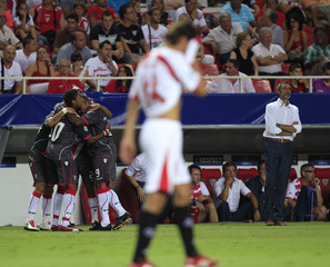 Braga players celebrate a goal by team mate Matheus as Sevilla's coach Antonio Alvarez looks on during their Champions League playoff soccer match at the Sanchez Pizjuan stadium in Seville