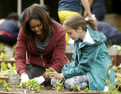 United States first Lady Obama plants vegetables with student Marley Santos during spring planting of the White House vegetable garden in Washington