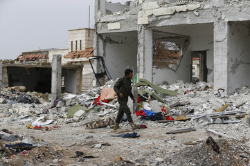 A fighter of the Kurdish People's Protection Units (YPG) walks past damaged buildings in the northern Syrian town of Kobani