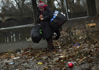 Mercado walks with her belongings to shelter during Nor'easter, in Rockaways section of Queens borough of New York