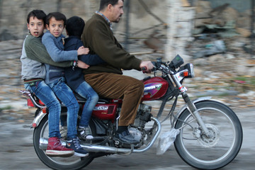 Boys ride a motorcycle with a man in rebel-held besieged old Aleppo