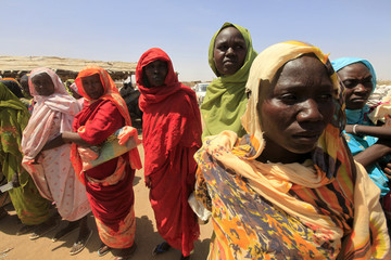 Displaced women wait to receive food at a food distribution centre as special envoys and diplomats arrive for a meeting to discuss the progress of a peace treaty in Darfur, at Shangli Tobay village