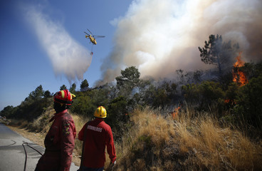 A helicopter drops water over a forest fire in Adsamu village, near Vouzela
