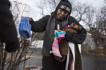 A protester hands out donated scarves, hats and gloves near the memorial for Antonio Martin, an armed 18-year old black teen who was fatally shot by police in Berkeley