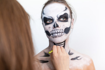 Make-up artist make the girl halloween make up on white background. Halloween face art.