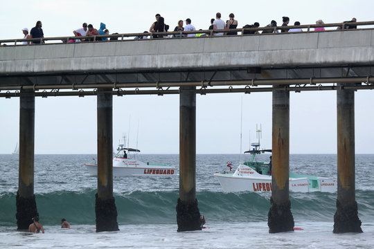 Lifeguard boats search the waters near a pier for victims of a lightning strike that injured people in Venice