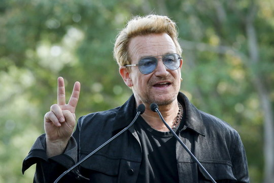 Irish singer Bono speaks to guests before the unveiling of a tapestry honoring John Lennon at Ellis Island in New York
