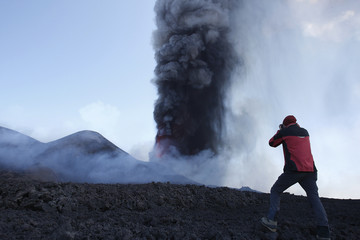 A man takes a picture as mount Etna spews volcanic ash during an eruption on the southern Italian island of Sicily