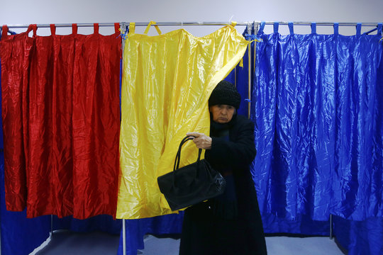 An elderly woman leaves a polling booth decorated with Romania's national flag colours at a voting station in Bucharest