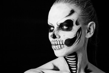 Girl with creative halloween face art on black background.