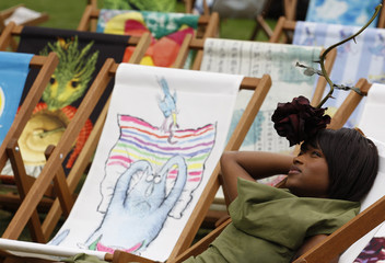 A model, wearing a hat designed by Philip Treacy, poses for photographers while sitting amongst deck chairs designed by various artists for the charity Deckchair Dreams, in Hyde Park in London