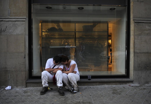 A couple sleeps in front of a shop window on the fifth day of the San Fermin festival in Pamplona