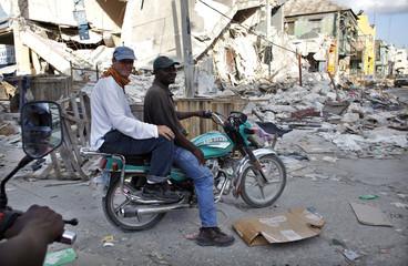 Caracas based Andean region bureau chief, Andy Cawthorne, sits on a bike in downtown Port-au-Prince