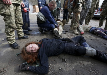 Rescuers and volunteers take part in an emergency medical training, as part of a civil defence course, in the village of Kapitanivka outside Kiev