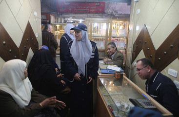 A Palestinian policewoman loyal to Hamas inspects a jewellery store in Gaza City
