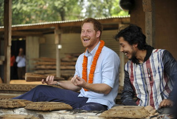 Britain's Prince Harry laughs as he tries wood carving at a heritage site in Patan Durbar Square in the outskirts of Kathmandu