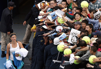 Belarus' Azarenka walks past members of the crowd wanting her autograph after she won her third round women's singles match against Russia's Vesnina at the China Open tennis tournament in Beijing