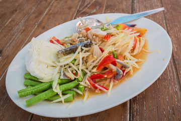 "Papaya Salad from Thailand, Thai food name is ""SOM TAM"" on the wooden table"