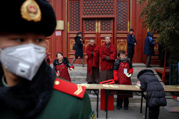 Buddhist monks stand behind a paramilitary policeman providing security as people gather to burn incense sticks and pray for good fortune at Yonghegong Lama Temple on the first day of the Lunar New Year of the Rooster in Beijing