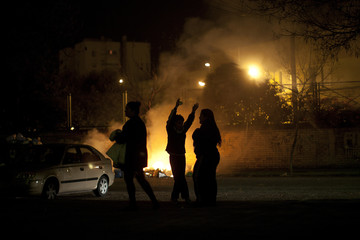 People stand near burning rubbish bags, which were set on fire by residents frustrated by piling rubbish due to a strike by garbage collectors in Jerez de la Frontera