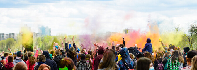 Holiday holi, young people in smoke dancing hands up outdoors