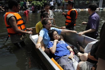 Thai rescue workers move a patient from a flooded area at Pathum Thani province