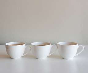 Three cups of white tea on a table against neutral wall background (selective focus)