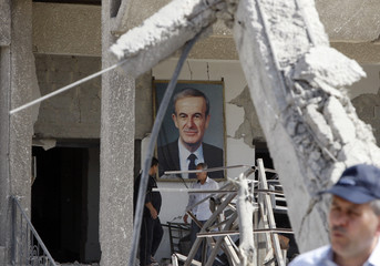 Framed portrait of Syria's late President Hafez al-Assad is seen at the site of an explosion in a security building in Damascus