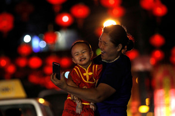 A woman and a boy take a picture in a street decorated with Chinese lamps to celebrate the Lunar New Year in Yangon