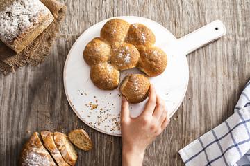 Female hand breaking freshly baked bread