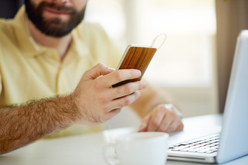 Businessman sitting in home office and using smartphone