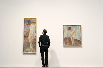 """Holden of the Tate poses with two paintings of Edvard Munch's """"Weeping Woman"""" series at the Tate Modern in London's Southbank"""