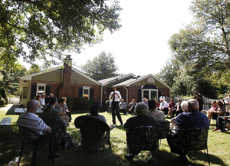 U.S. President Barack Obama answers questions from residents and small business owners in yard of a residential house in Fairfax, Virginia