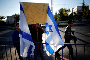 An Israeli man holds a picture depicting the peace symbol of dove with an olive branch next to Israeli flags as a border policeman secures area near entrance to Mount Herzl cemetery ahead of the funeral of former Israeli President Shimon Peres in Jerusalem