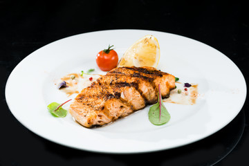 Grilled salmon steak on a dark background