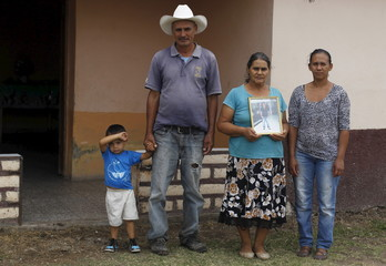 Benjamin Aceituno and his wife Ana Rodas pose with a picture of their missing son at the town of the Ermita outside Tegucigalpa
