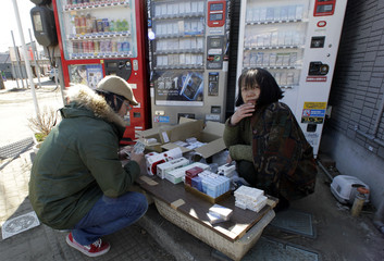 A woman sells cigarettes next to vending machines broken by the March 11 earthquake and tsunami in Higashi-Matsushima