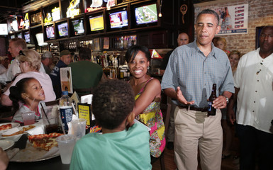 U.S. President Barack Obama greets a family at Ziggy's Pub in Amherst