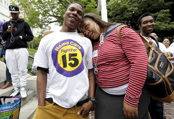 Dowdell and Scott celebrate after the Los Angeles City Council approved a proposal to increase the minimum wage to $15.00 per hour in Los Angeles, California