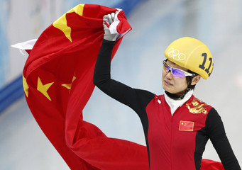 China's Li Jianrou celebrates with her country's flag after winning the women's 500 metres short track speed skating final event at the Iceberg Skating Palace during the 2014 Sochi Winter Olympics