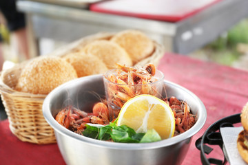 Bowl with shrimps and rolls in wicker basket