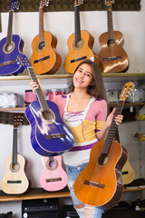 Teenage girl selecting guitar in shop.