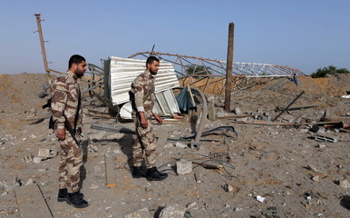 Members of Palestinian security forces loyal to Hamas survey a Hamas site after it was hit by an Israeli airstrike in Rafah in the southern Gaza Strip