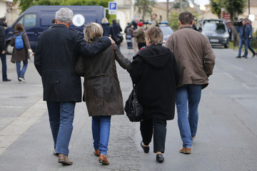 People comfort each other as they walk in the street in Puisseguin the day after 41 people perished in a bus accident