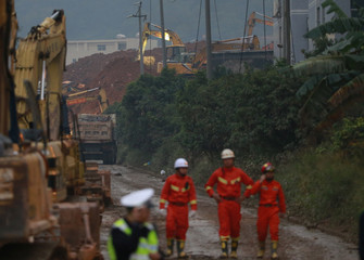 Rescuers walk next to excavators working at the site to search for landslide survivors among debris of destroyed buildings in Shenzhen