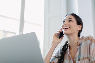 Woman speaking on phone while working with laptop