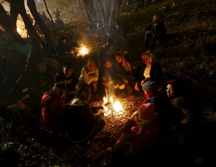 Migrants sit around a fire as they wait to cross the Austrian border in Spielfeld near the village of Sentilj