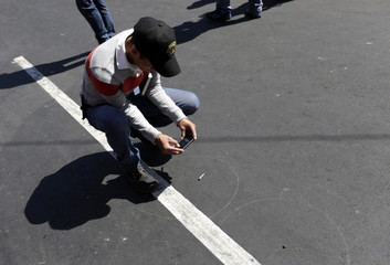 A police officer take a picture of a shell casing at a crime scene outside the San Juan De Dios Hospital, Guatemala City
